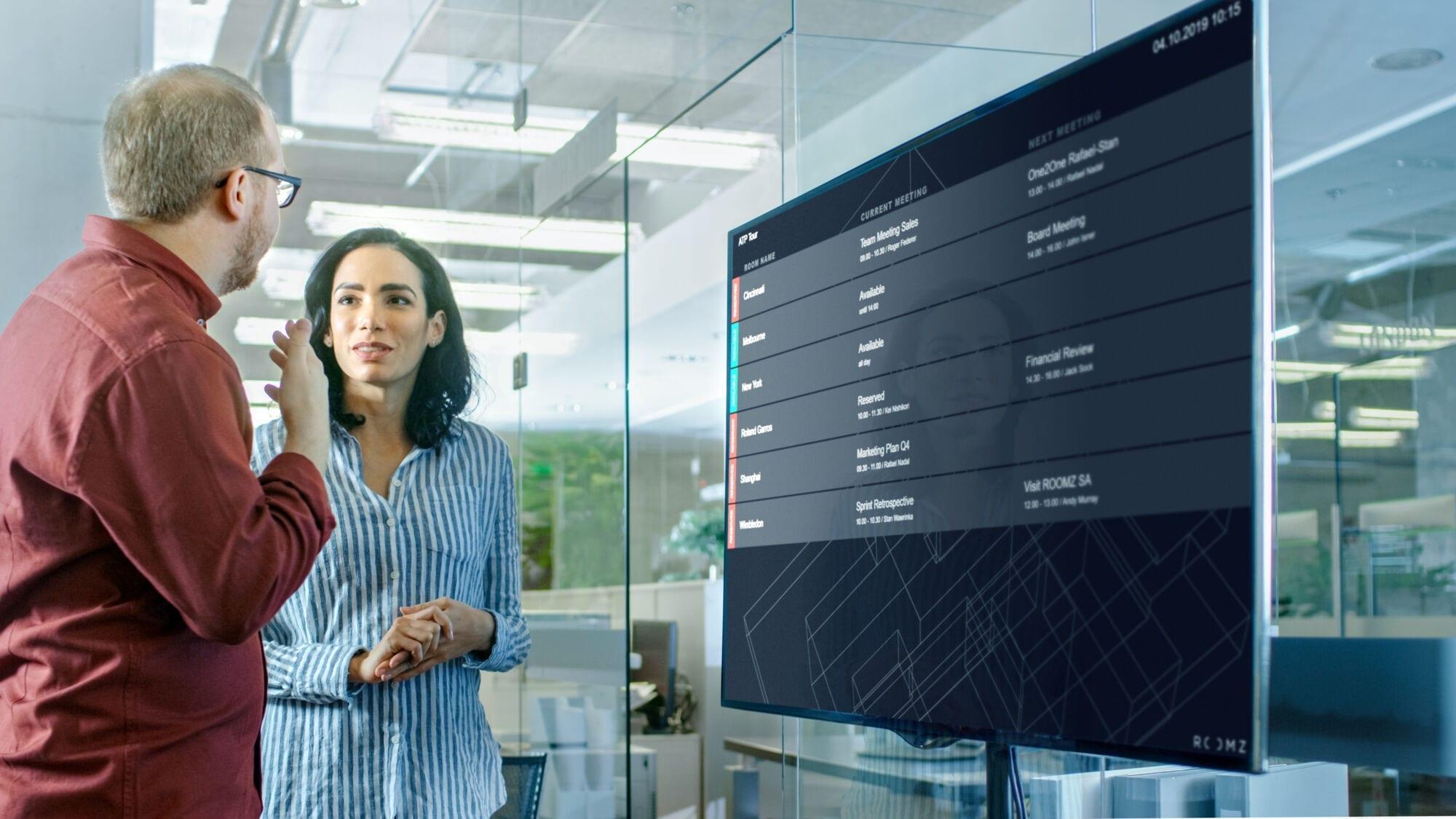 Mitarbeiter studieren die digtialen Grundrisse ihrer Firma am ROOMZ Viewer Flightboard, um einen freien Meetingsraum zu finden.